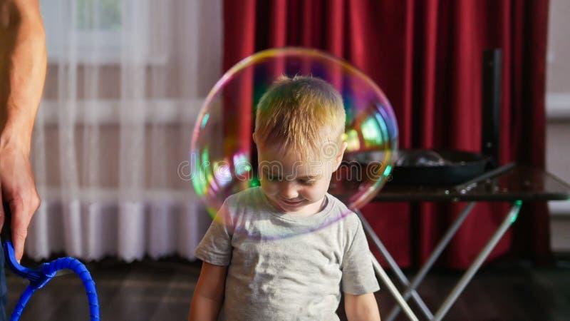 Bebé sonriente lindo con la burbuja de jabón grande imagen de archivo