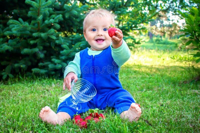 Bebé sonriente lindo que se sienta en una hierba verde fresca en un parque y que da la fresa al espectador foto de archivo