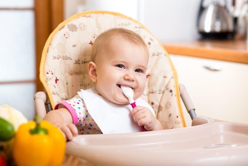 Bebé sonriente que come la comida en cocina foto de archivo