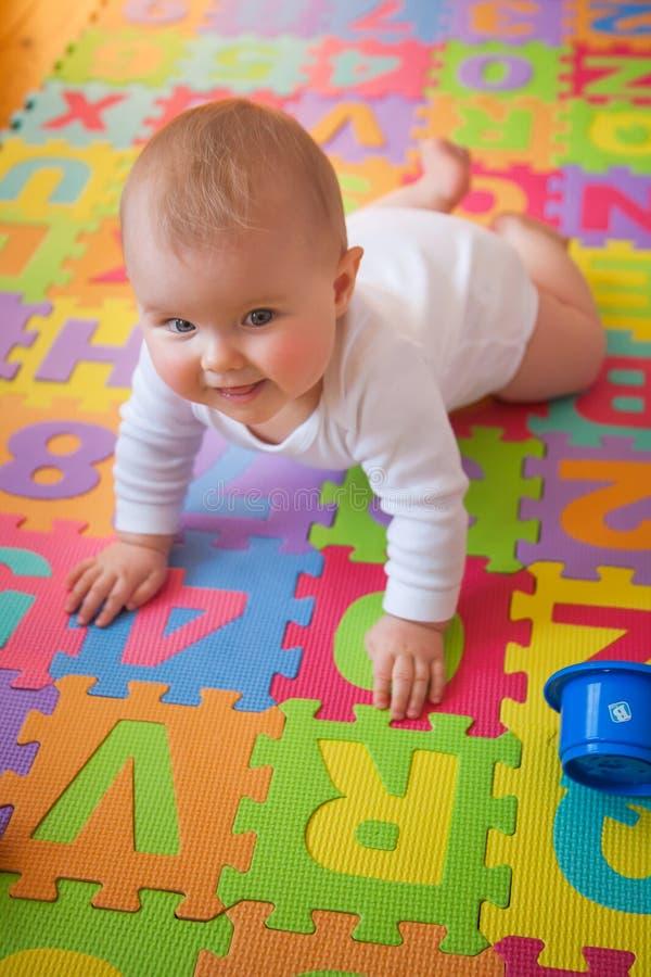 Bebé sonriente que se arrastra en la estera del alfabeto fotografía de archivo