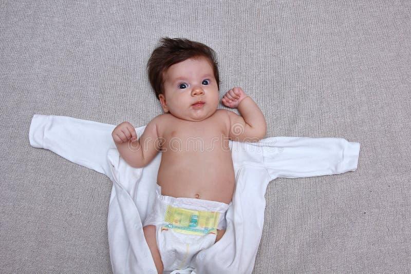 Bebé sorprendido fuera de la ropa del cuerpo imagenes de archivo