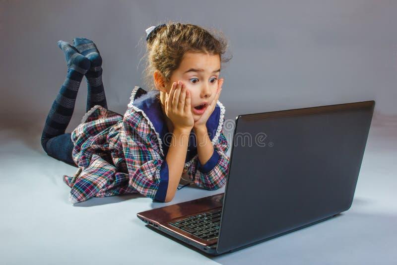 Bebé sorprendido mirando el ordenador en gris fotos de archivo libres de regalías