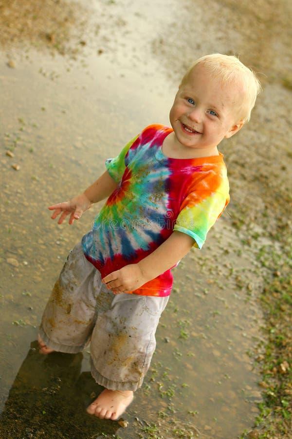 Bebé sucio lindo en charco de la lluvia imágenes de archivo libres de regalías