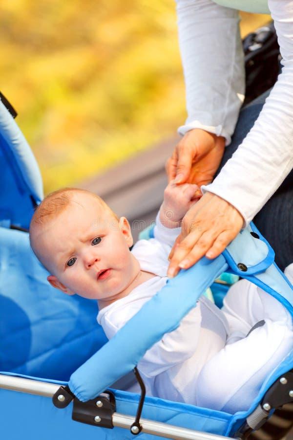 Bebé surpreendido que senta-se no carrinho de criança no parque fotografia de stock royalty free