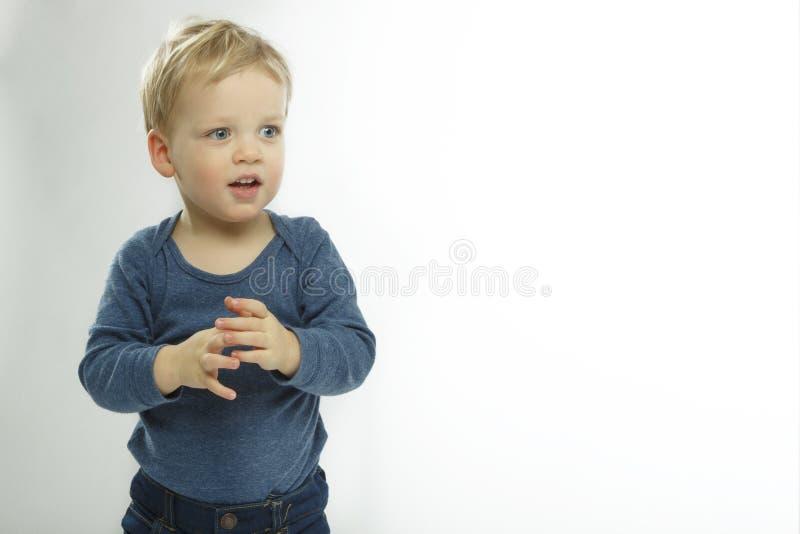 Bebé tímido en el fondo blanco Niño lindo con pedir la expresión de la cara El pedir adorable del niño qué se está encendiendo  imagen de archivo libre de regalías