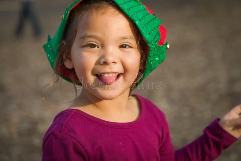 Bebé tonto de los jóvenes de la raza mixta que tiene sombrero de la Navidad de la diversión que lleva foto de archivo