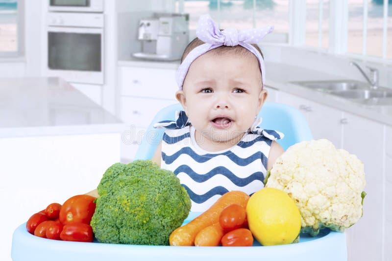 Bebé triste con las verduras en cocina imagenes de archivo