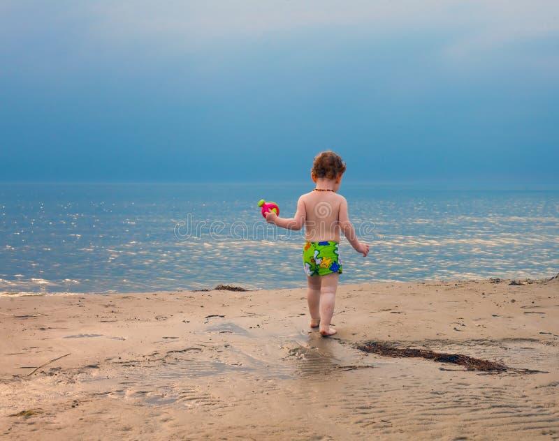 Bebé waling en la playa en la puesta del sol foto de archivo libre de regalías
