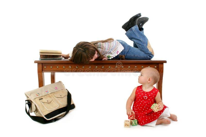 Bebé y hermana grande que cuelgan hacia fuera foto de archivo