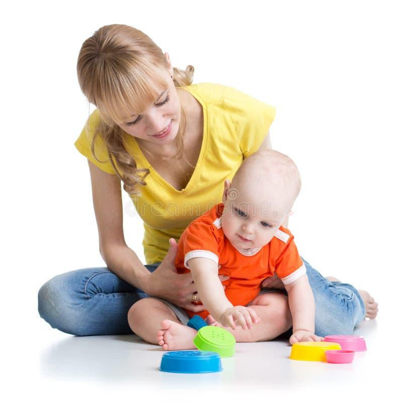 Bebé y madre que juegan así como los juguetes coloridos imagen de archivo