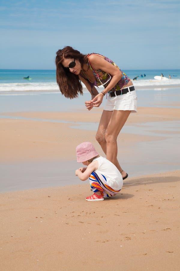 Bebé y madre que recogen cáscaras del mar fotos de archivo libres de regalías