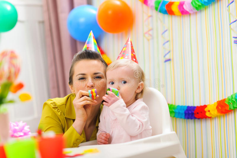 Bebé y madre que soplan en el claxon del partido imagen de archivo libre de regalías
