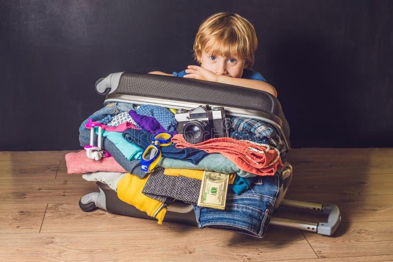 Bebé y maleta del viaje Niño y equipaje llenos para las vacaciones por completo del viaje de la ropa, del niño y de la familia imágenes de archivo libres de regalías