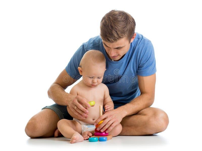 Bebé y padre que juegan así como el juguete de la pirámide foto de archivo