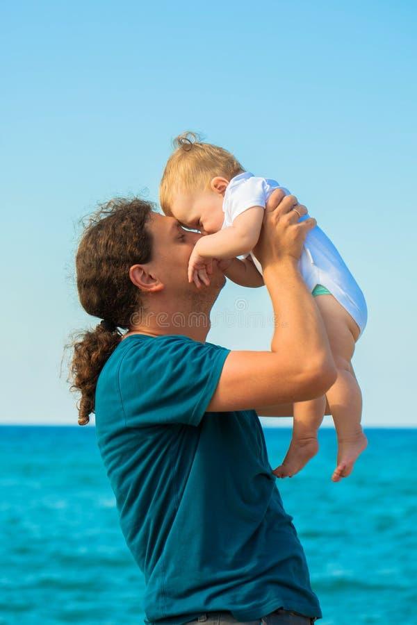 Bebé y padre que se divierten junto en la playa fotografía de archivo