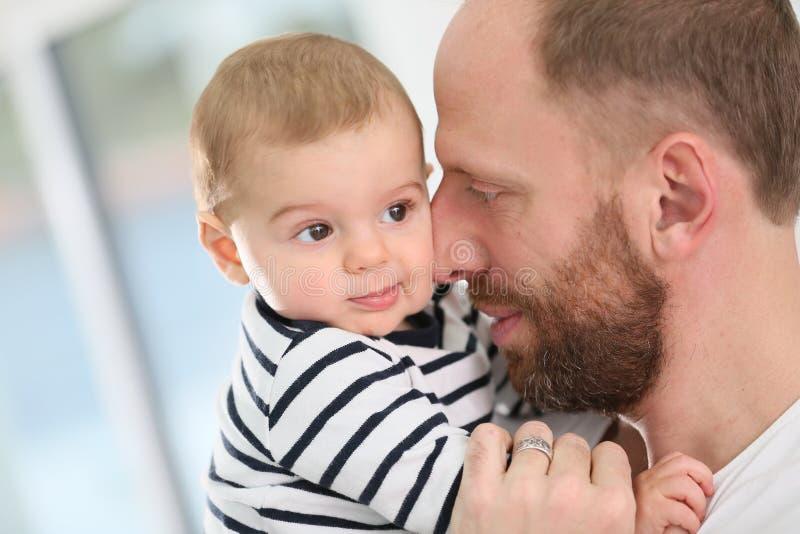 Bebé y su padre que abrazan imagenes de archivo