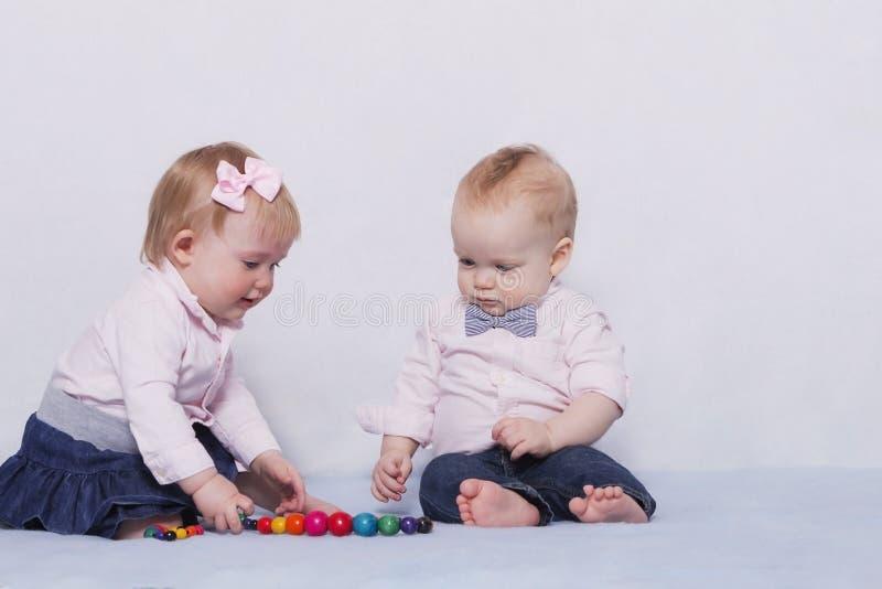 Bebés infantiles lindos que juegan con las gotas coloridas fotos de archivo