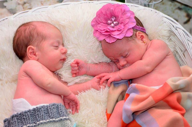 Bebés, muchacha gemela y muchacho durmiendo en la cesta blanca fotos de archivo libres de regalías