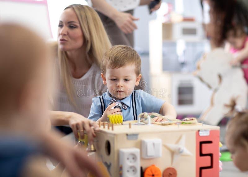 Bebés que juegan en centro o cuarto de niños de guardería imagen de archivo