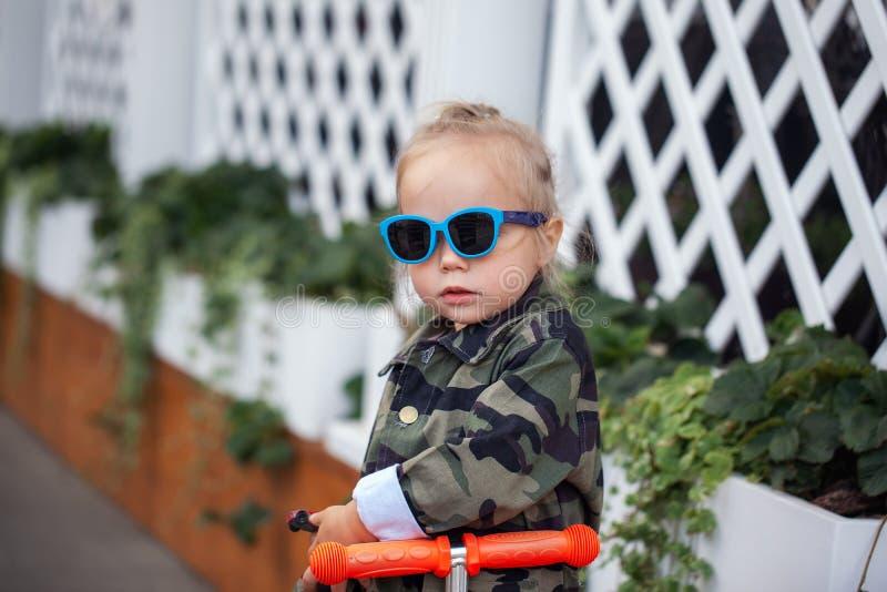 Bebê à moda fresco nos óculos de sol no 'trotinette' na rua foto de stock