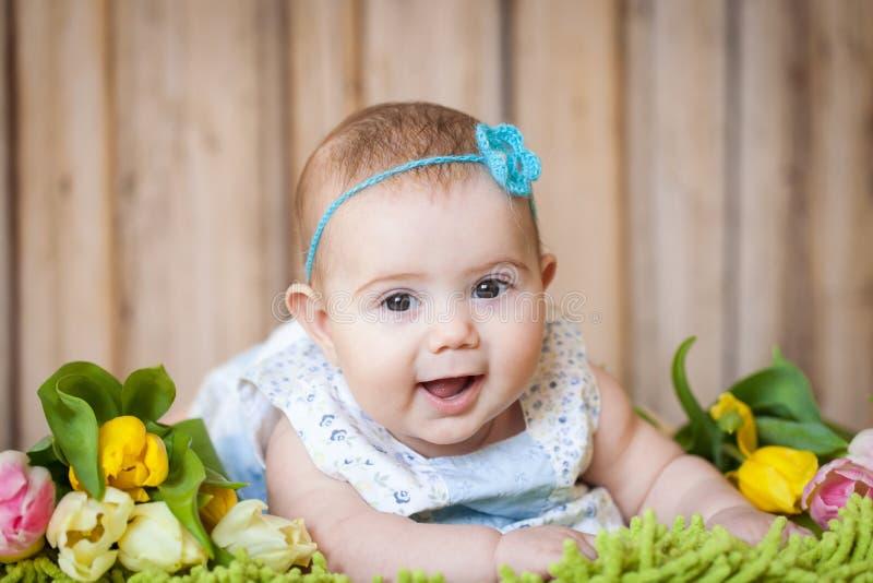 Bebê adorável com tulipas fotografia de stock royalty free