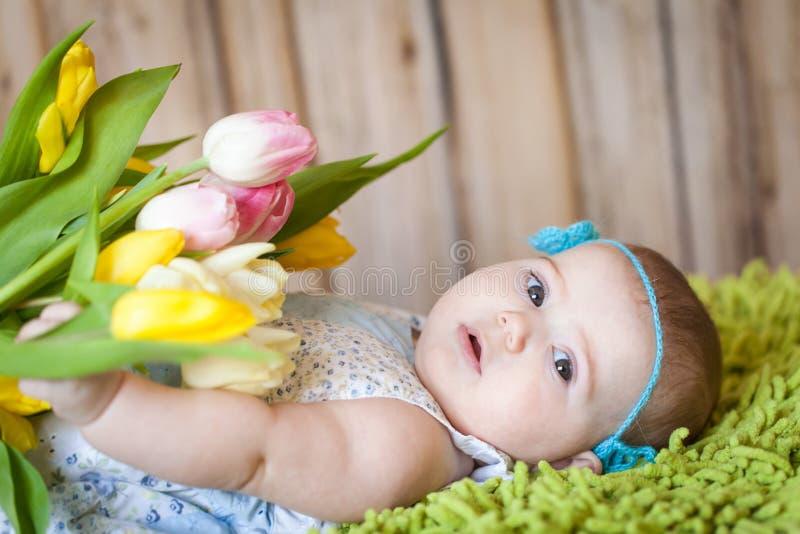 Bebê adorável com tulipas fotos de stock royalty free