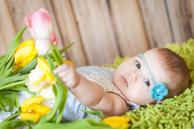 Bebê adorável com tulipas foto de stock