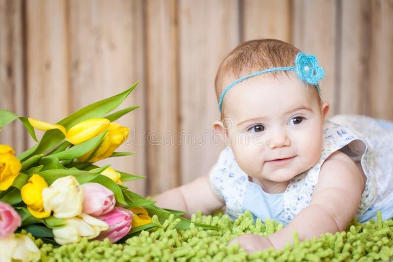 Bebê adorável com tulipas fotografia de stock