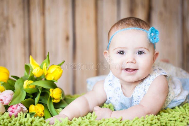 Bebê adorável com tulipas imagens de stock royalty free
