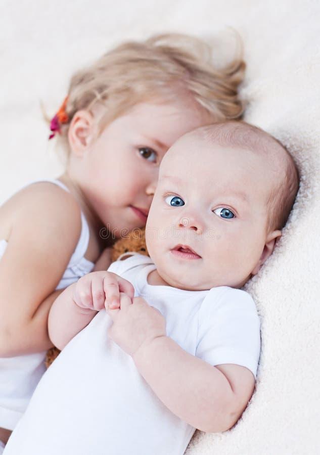Bebê adorável e sua irmã mais idosa foto de stock royalty free