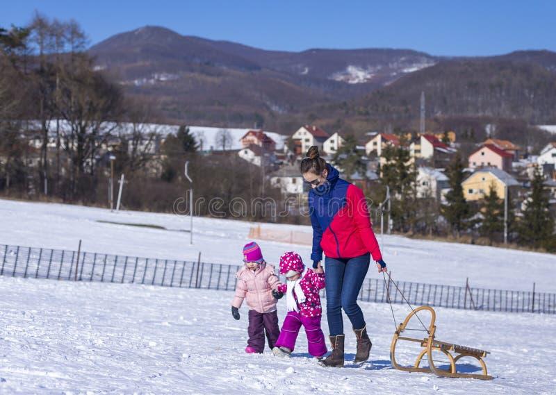 Bebê adorável em uma neve branca na situação morna do terno na neve foto de stock royalty free