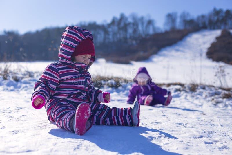 Bebê adorável em uma neve branca na situação morna do terno na neve fotografia de stock