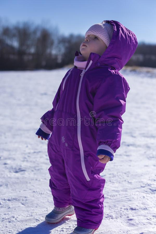 Bebê adorável em uma neve branca na situação morna do terno na neve imagem de stock royalty free