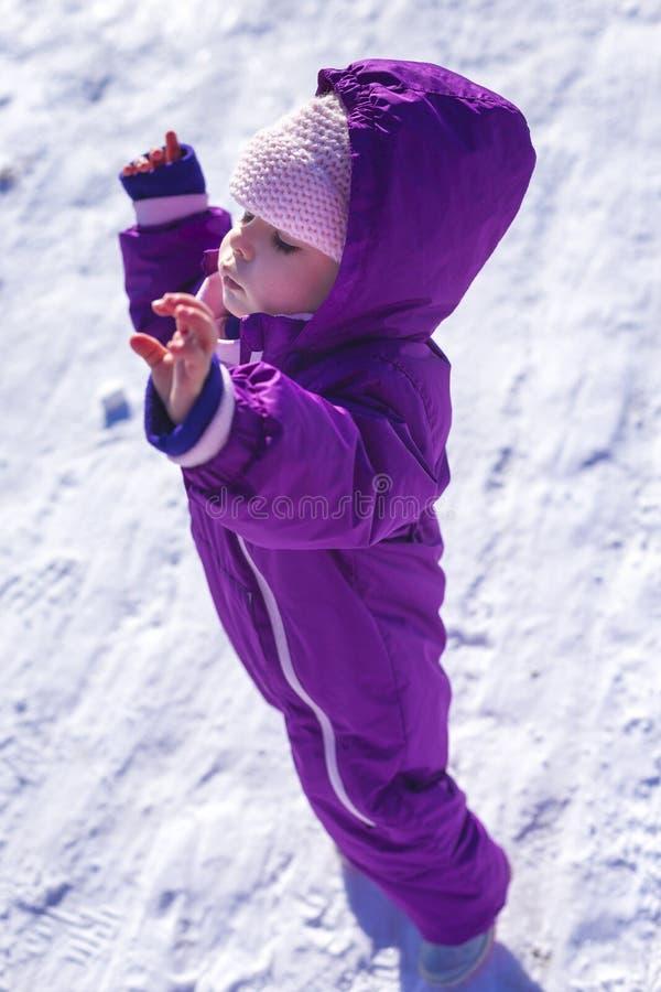 Bebê adorável em uma neve branca na situação morna do terno na neve foto de stock