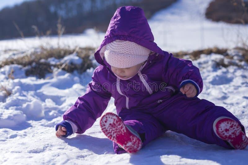 Bebê adorável em uma neve branca na situação morna do terno na neve imagens de stock