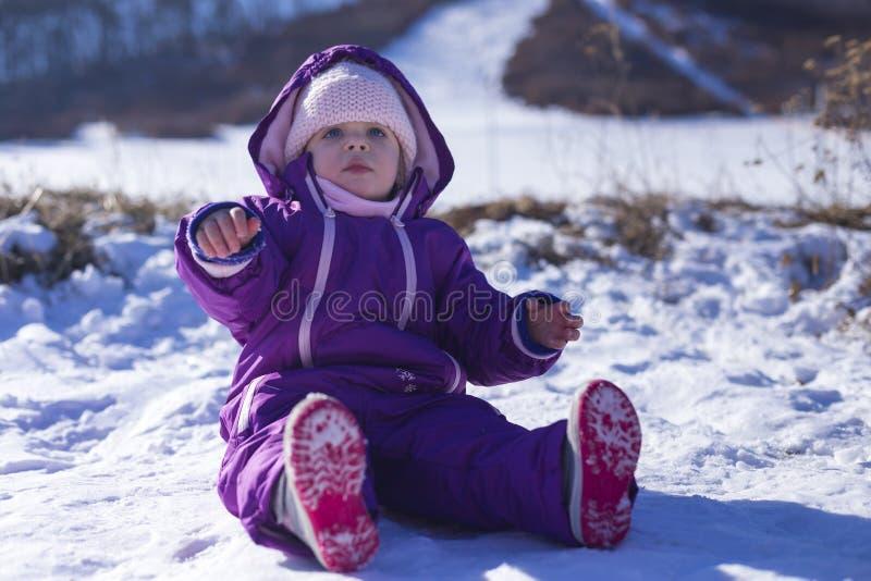 Bebê adorável em uma neve branca na situação morna do terno na neve imagens de stock royalty free