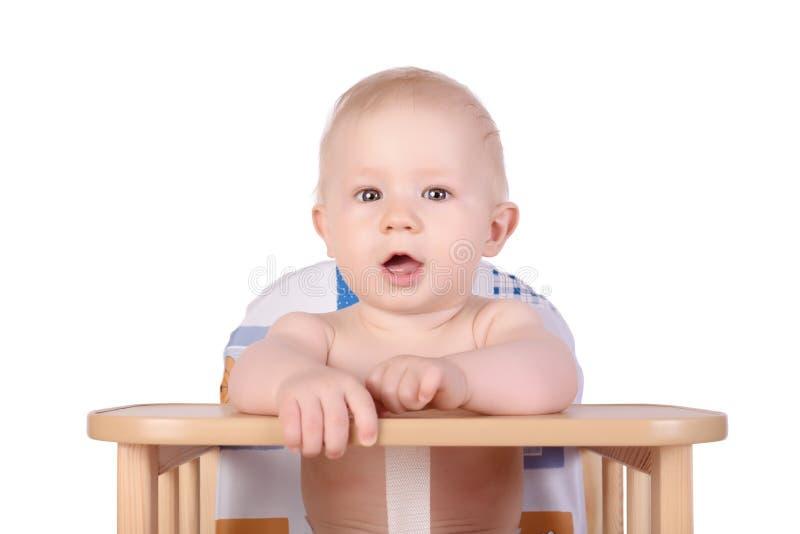 Bebê adorável na cadeira alta isolada imagem de stock