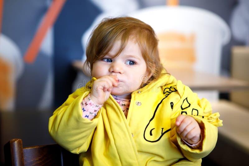 Bebê adorável pequeno bonito que senta-se no café interno Criança feliz da criança que come o pão imagem de stock