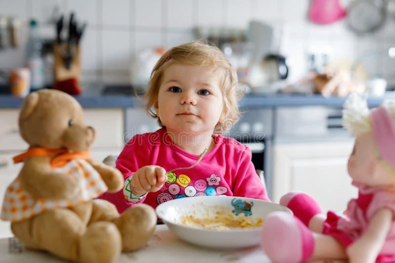 Bebê adorável que come dos vegetais e da massa da forquilha Pouca alimentação de crianças e jogo com boneca do brinquedo foto de stock