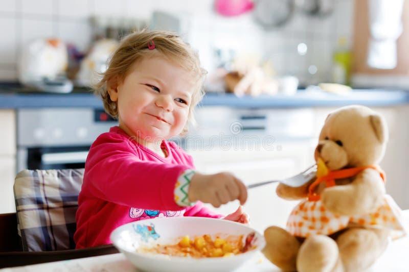 Bebê adorável que come dos vegetais e da massa da forquilha Pouca alimentação de crianças e jogo com o urso de peluche do brinque fotos de stock