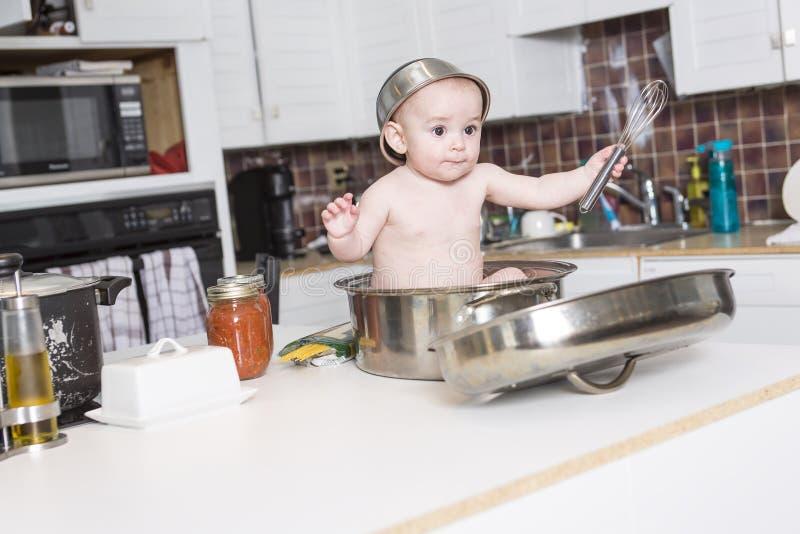 Bebê adorável que cozinha na cozinha fotografia de stock royalty free