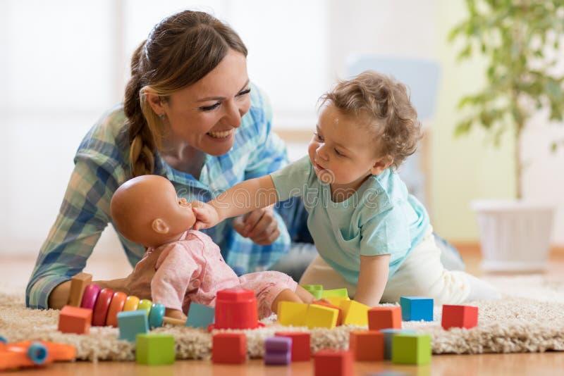 Bebê adorável que joga com a boneca no berçário Criança saudável feliz que tem o divertimento com os brinquedos diferentes colori imagens de stock