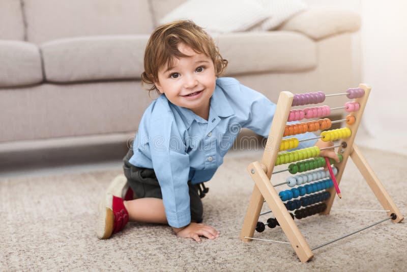 Bebê adorável que joga com contagens coloridas em casa fotos de stock royalty free