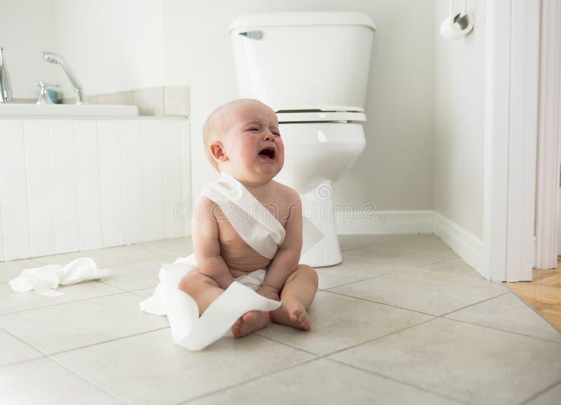 Bebê adorável que joga com papel higiênico fotos de stock