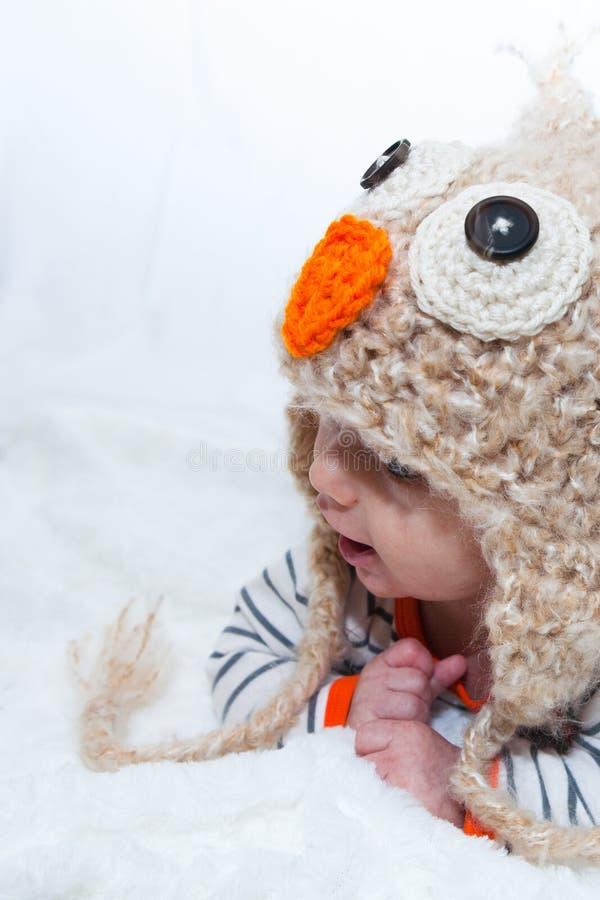 Bebê adorável que olha ao lado em Owl Hat foto de stock