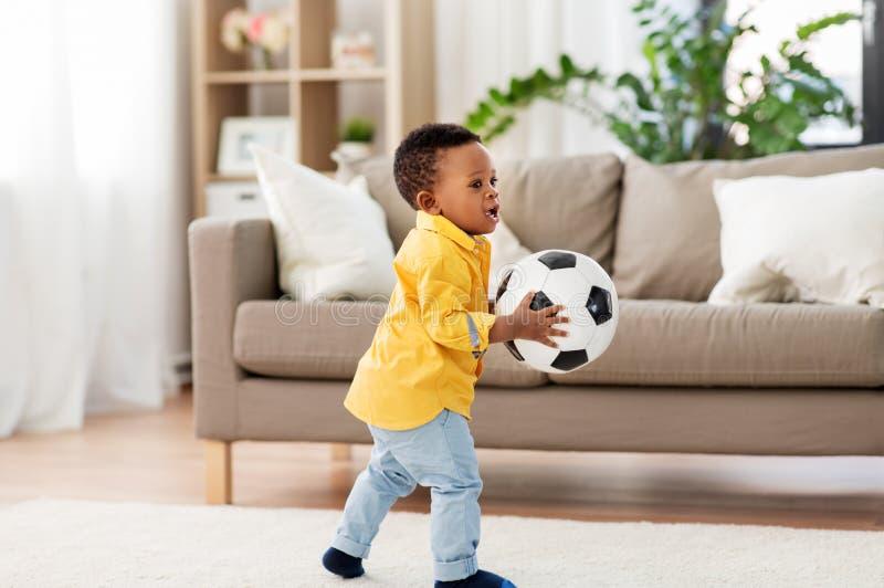 Bebê afro-americano que joga com bola de futebol fotografia de stock royalty free
