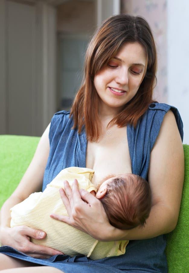 Bebê amamentando de sorriso da matriz imagem de stock