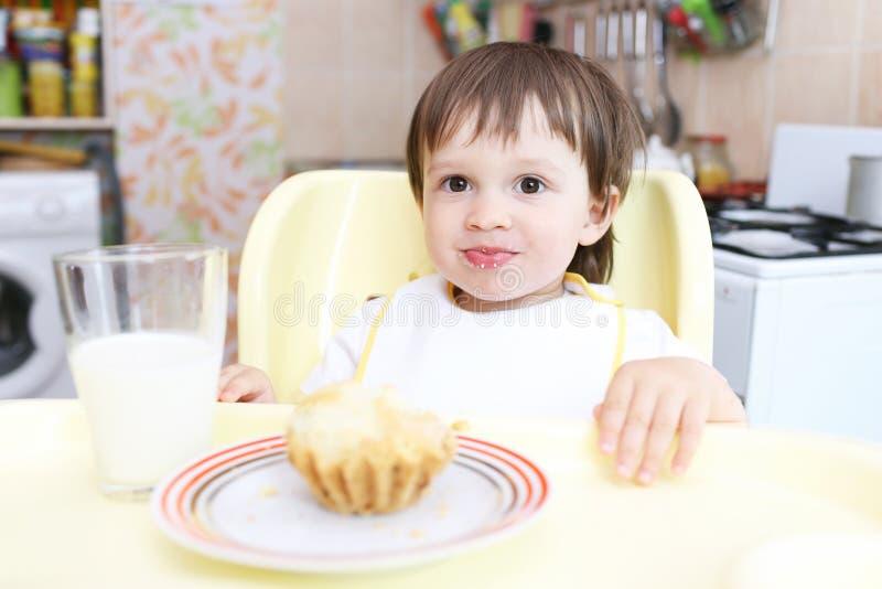 Bebê amusing que come o queque e o leite foto de stock