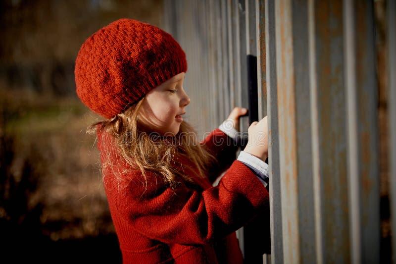 Bebê 3 anos com cabelo longo Em suportes de uma boina vermelha e do revestimento na rua na luz do sol, perto da cerca imagem de stock