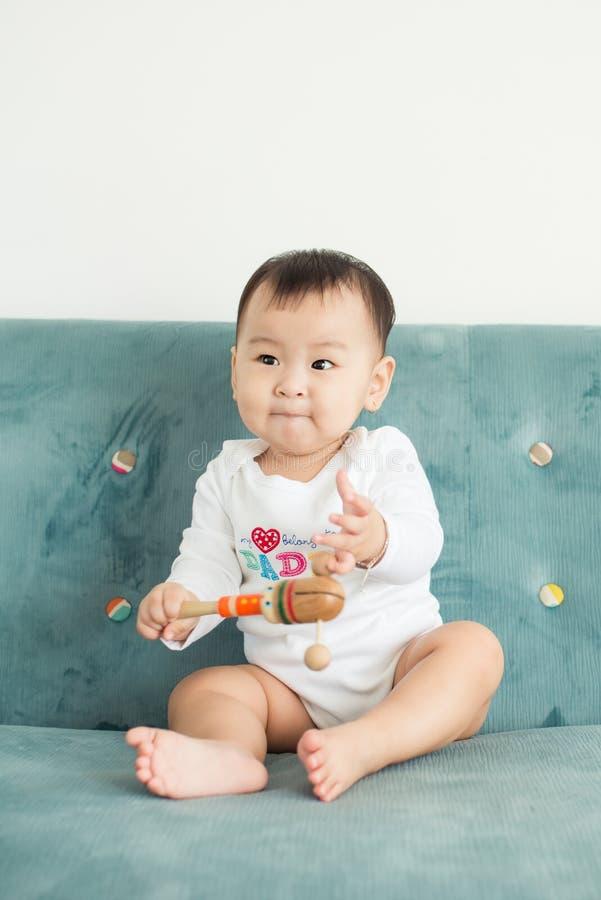Bebê asiático bonito que senta-se na cama em sua sala foto de stock royalty free